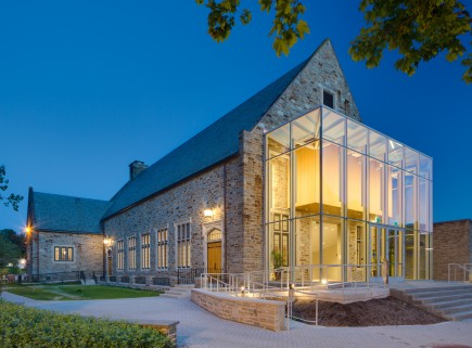The modern glass entry addition provides an obvious contrast to the Butler Stone building with vertical proportions that respond to the Gothic context utilizing standard construction.-Friends School of Baltimore Performing and Visual Arts Center
